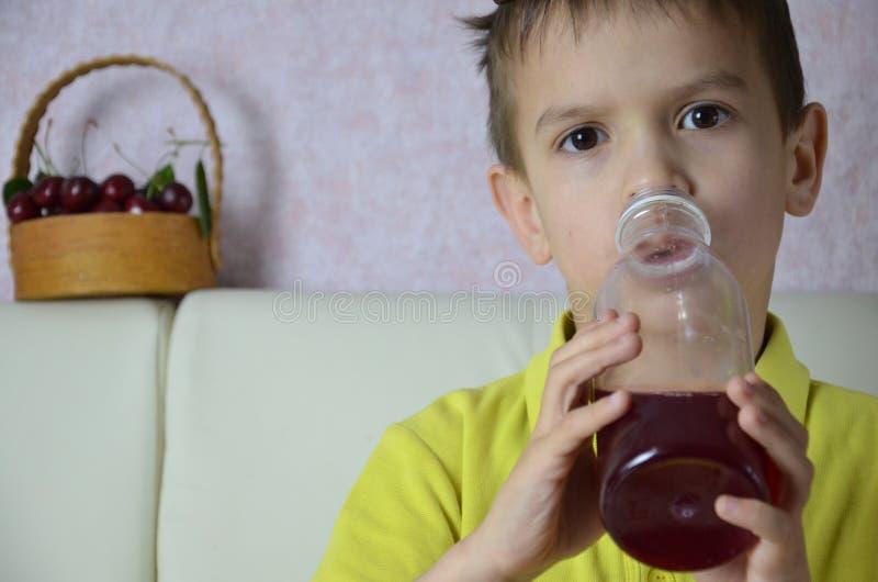 Χαριτωμένος χυμός κατανάλωσης μικρών παιδιών στο σπίτι, ποτά χυμού κερασιών από ένα μπουκάλι ή ένα γυαλί με ένα άχυρο στοκ φωτογραφίες με δικαίωμα ελεύθερης χρήσης