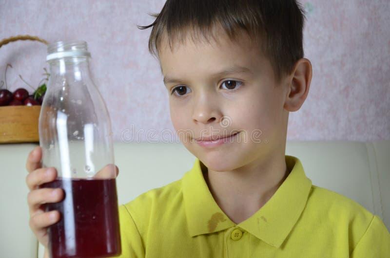 Χαριτωμένος χυμός κατανάλωσης μικρών παιδιών στο σπίτι, ποτά χυμού κερασιών από ένα μπουκάλι ή ένα γυαλί με ένα άχυρο στοκ φωτογραφία