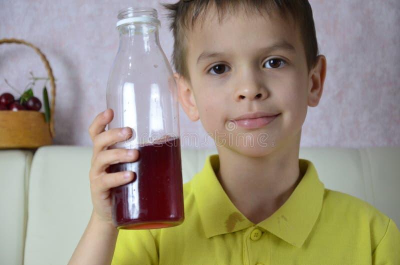 Χαριτωμένος χυμός κατανάλωσης μικρών παιδιών στο σπίτι, ποτά χυμού κερασιών από ένα μπουκάλι ή ένα γυαλί με ένα άχυρο στοκ εικόνες
