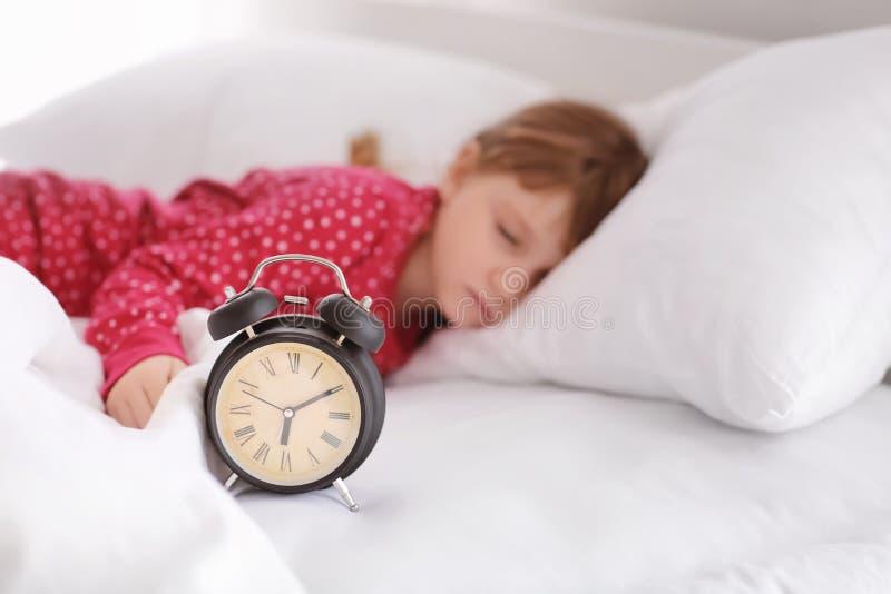 Χαριτωμένος ύπνος μικρών κοριτσιών στο κρεβάτι με το ξυπνητήρι στοκ φωτογραφίες