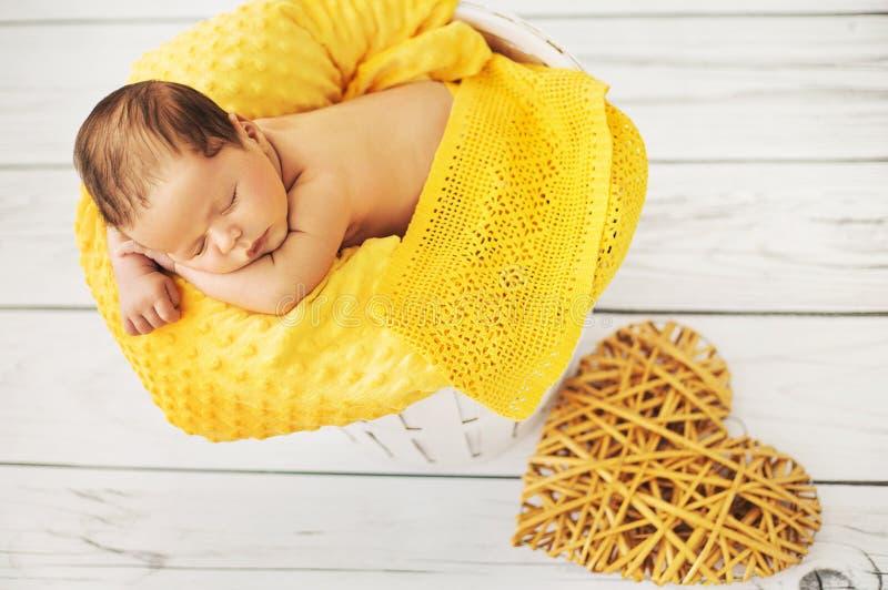 Χαριτωμένος ύπνος μωρών σε ένα κίτρινο κάλυμμα στοκ εικόνες