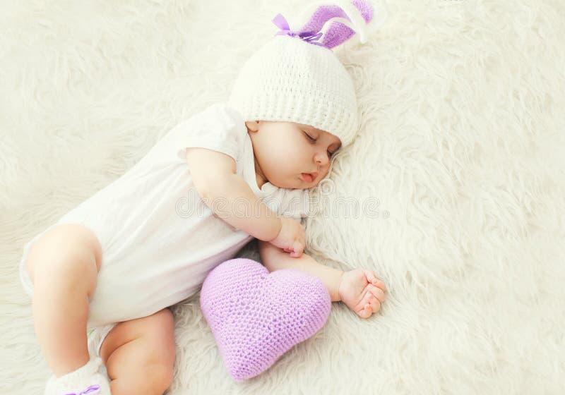 Χαριτωμένος ύπνος μωρών στο άσπρο κρεβάτι στο σπίτι με την πλεκτή καρδιά μαξιλαριών στοκ φωτογραφίες