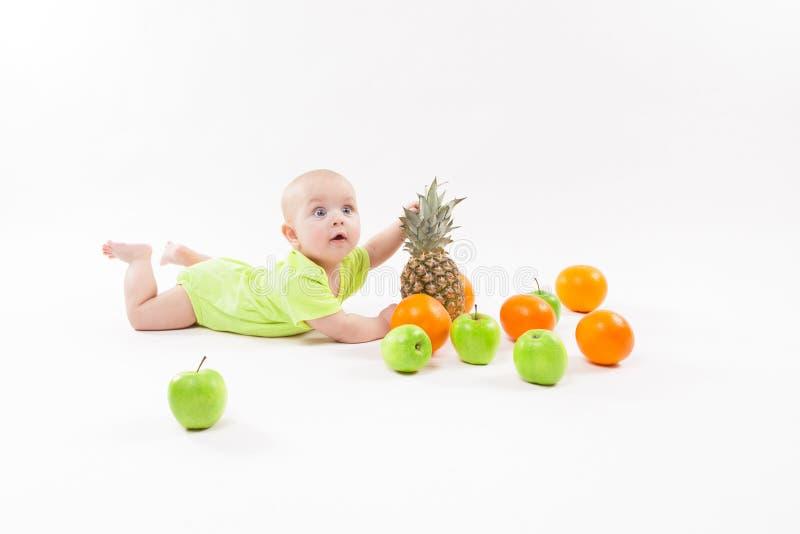 Χαριτωμένο έκπληκτο μωρό που φαίνεται φρούτα στο άσπρο υπόβαθρο συμπεριλαμβανομένου στοκ εικόνες