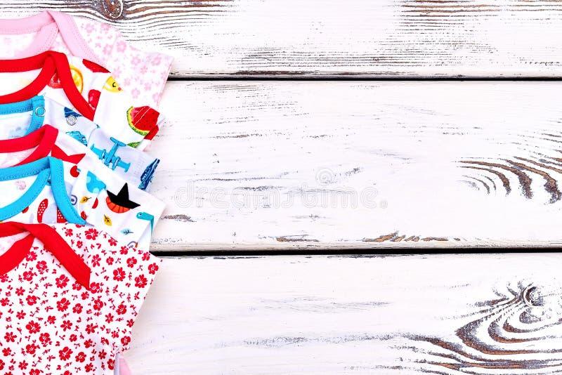 Χαριτωμένο ένδυμα μωρών, ξύλινο υπόβαθρο στοκ εικόνες