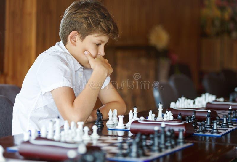 Χαριτωμένο, έξυπνος, χρονών το αγόρι 11 στο άσπρο πουκάμισο κάθεται στην τάξη και παίζει το σκάκι στη σκακιέρα Κατάρτιση, μάθημα, στοκ φωτογραφία με δικαίωμα ελεύθερης χρήσης