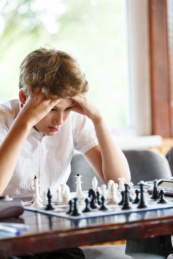 Χαριτωμένο, έξυπνος, χρονών το αγόρι 11 στο άσπρο πουκάμισο κάθεται στην τάξη και παίζει το σκάκι στη σκακιέρα Κατάρτιση, μάθημα, στοκ εικόνες με δικαίωμα ελεύθερης χρήσης