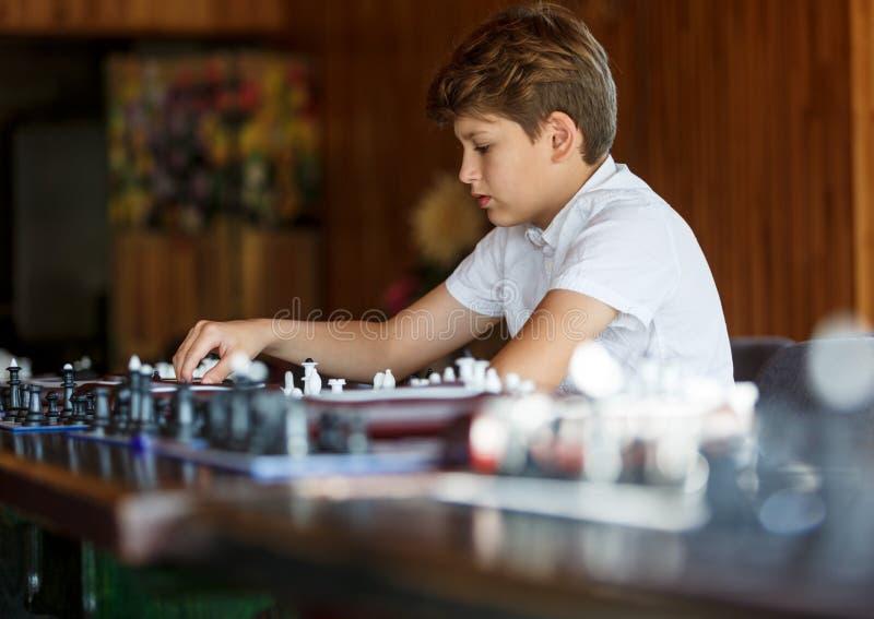 Χαριτωμένο, έξυπνος, χρονών το αγόρι 11 στο άσπρο πουκάμισο κάθεται στην τάξη και παίζει το σκάκι στη σκακιέρα Κατάρτιση, μάθημα, στοκ φωτογραφία