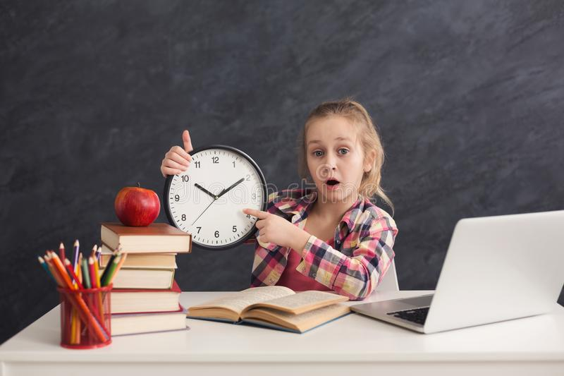 Χαριτωμένο έξυπνο ρολόι εκμετάλλευσης κοριτσιών και υπόδειξη σε το στοκ εικόνες με δικαίωμα ελεύθερης χρήσης