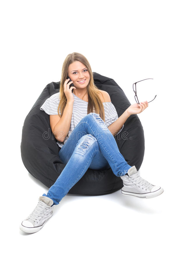 Χαριτωμένο έφηβη που μιλά στην τηλεφωνική συνεδρίαση στο beanbag στοκ φωτογραφία με δικαίωμα ελεύθερης χρήσης