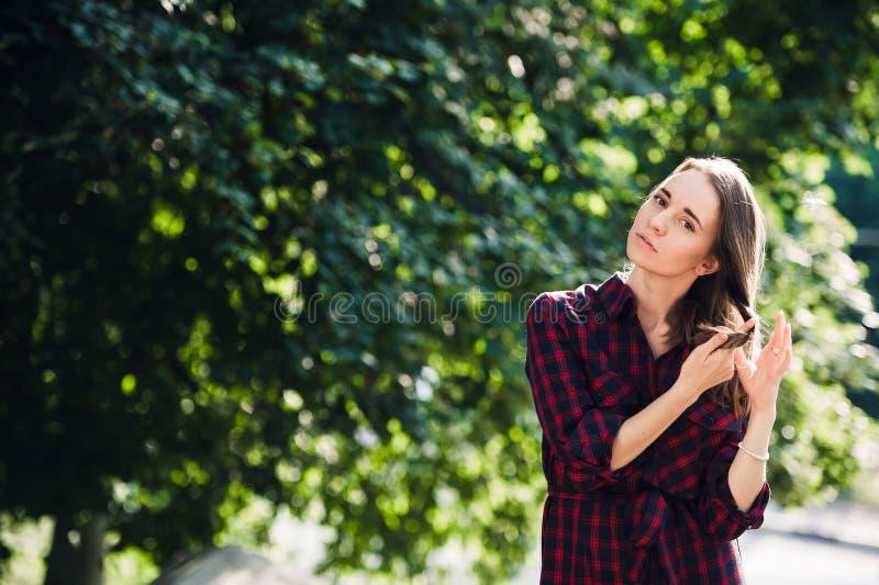 Χαριτωμένο έφηβη στο περιστασιακό παιχνίδι φορεμάτων με τις πλεξούδες της, εξέταση τη κάμερα και χαμόγελο, που στέκονται ενάντια  στοκ εικόνες με δικαίωμα ελεύθερης χρήσης