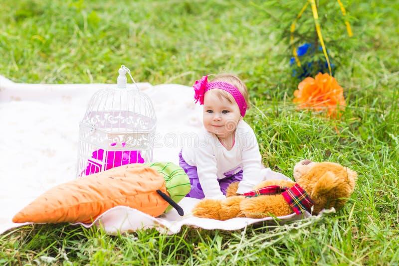 Χαριτωμένο λίγο ευτυχές κοριτσάκι με μεγάλο καφετή teddy αφορά το πράσινο λιβάδι χλόης, άνοιξη ή θερινή περίοδο στοκ φωτογραφία