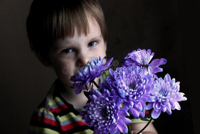 Χαριτωμένο αγοράκι που εξετάζει τα bellflowers, εκλεκτική εστίαση στοκ φωτογραφία με δικαίωμα ελεύθερης χρήσης
