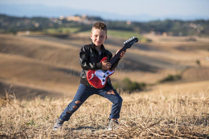 Χαριτωμένο αγόρι με μια κιθάρα στοκ φωτογραφία