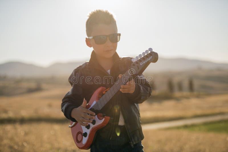 Χαριτωμένο αγόρι με μια κιθάρα στοκ εικόνες