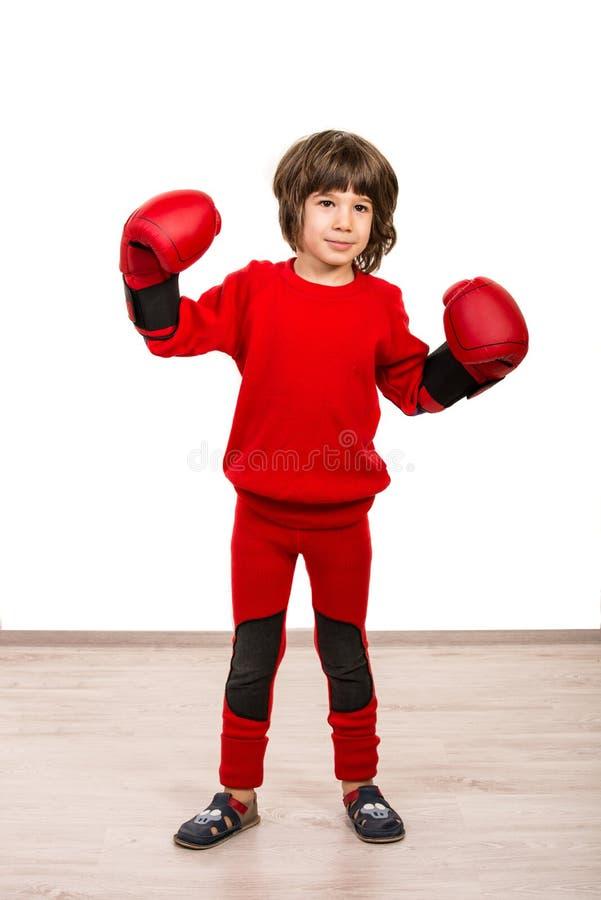 Χαριτωμένο αγόρι με τα εγκιβωτίζοντας γάντια που παρουσιάζουν πυγμές στοκ φωτογραφία με δικαίωμα ελεύθερης χρήσης