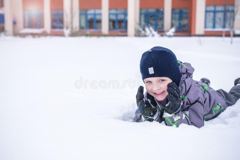 Χαριτωμένο αγόρι παιδάκι στα ζωηρόχρωμα χειμερινά ενδύματα που καθορίζουν επάνω Ενεργός υπαίθρια ελεύθερος χρόνος με τα παιδιά μέ στοκ φωτογραφία