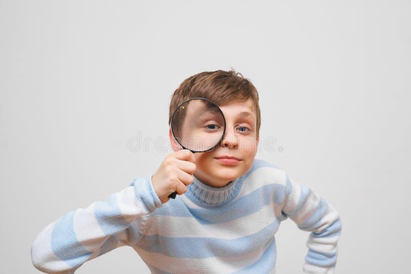 Χαριτωμένο αγόρι που εξετάζει τη κάμερα μέσω της ενίσχυσης - γυαλί, στο άσπρο BA στοκ εικόνες
