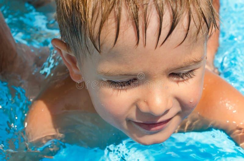 Χαριτωμένο αγόρι που κολυμπά στη λίμνη στοκ εικόνες