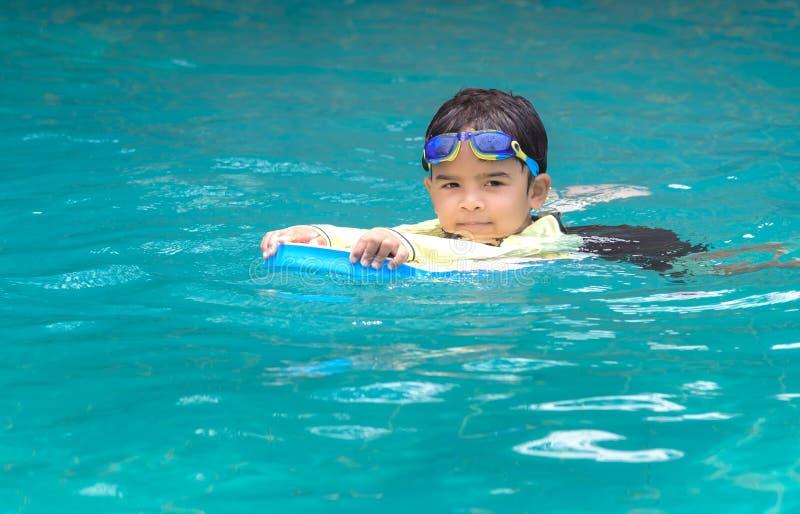 Χαριτωμένο αγόρι που μαθαίνει να κολυμπά στοκ φωτογραφία