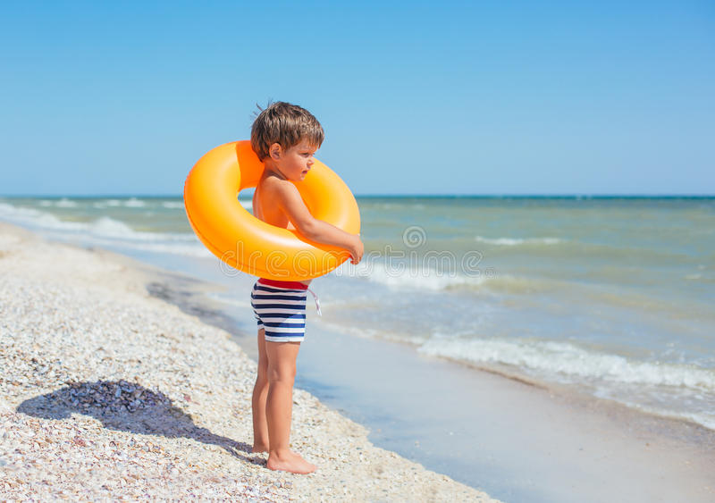 Χαριτωμένο αγόρι στη θερινή παραλία στοκ εικόνες