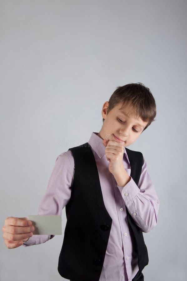 Χαριτωμένο αγόρι στο επιχειρησιακό κοστούμι που κρατά την άσπρη κάρτα και τη σκέψη στοκ εικόνα με δικαίωμα ελεύθερης χρήσης