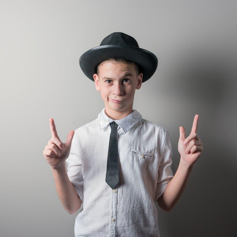Χαριτωμένο αγόρι στο μαύρο καπέλο και λευκό πουκάμισο στο φωτεινό υπόβαθρο στοκ εικόνα