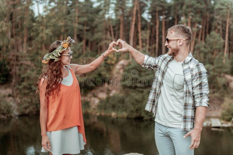 Χαριτωμένο ακτινοβολώντας ζεύγος που φορά τα γυαλιά ηλίου που αισθάνονται το εξαιρετικά ευτυχές ταξίδι από κοινού στοκ εικόνα