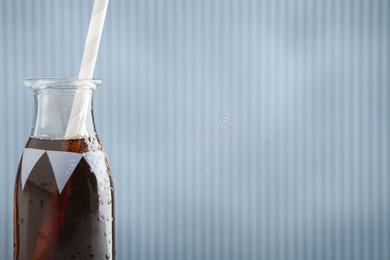 Χαριτωμένο αναδρομικό μπουκάλι σόδας με την κόλα και το άχυρο και το υπόβαθρο στοκ εικόνες με δικαίωμα ελεύθερης χρήσης