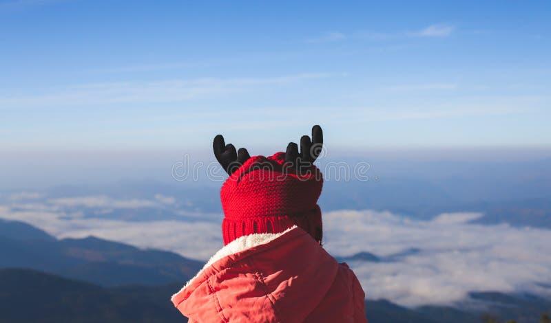 Χαριτωμένο ασιατικό κορίτσι παιδιών που φορά το πουλόβερ και το θερμό καπέλο που κοιτάζουν στην όμορφη φύση υδρονέφωσης και βουνώ στοκ εικόνα