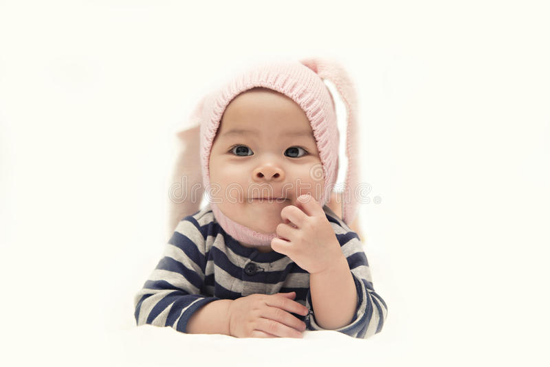 Χαριτωμένο ασιατικό κοριτσάκι με το ρόδινο καπέλο κουνελιών στο άσπρο υπόβαθρο στοκ φωτογραφία