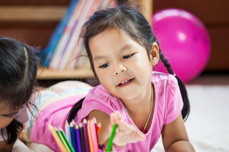 Χαριτωμένο ασιατικό μικρό κορίτσι που έχει τη διασκέδαση για να χρωματίσει με το κραγιόνι στοκ φωτογραφία με δικαίωμα ελεύθερης χρήσης