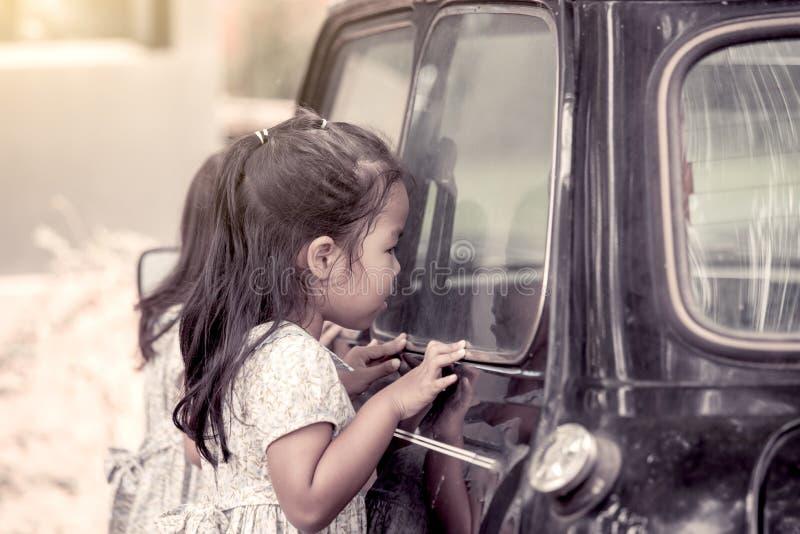 Χαριτωμένο ασιατικό μικρό κορίτσι που κοιτάζει μέσω του καθρέφτη αυτοκινήτων στοκ φωτογραφία