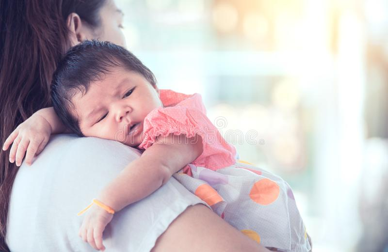 Χαριτωμένο ασιατικό νεογέννητο κοριτσάκι που στηρίζεται στον ώμο μητέρων ` s στοκ φωτογραφία με δικαίωμα ελεύθερης χρήσης