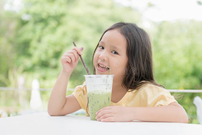 Χαριτωμένο ασιατικό πράσινο τσάι γάλακτος πάγου κατανάλωσης κοριτσιών στοκ φωτογραφία