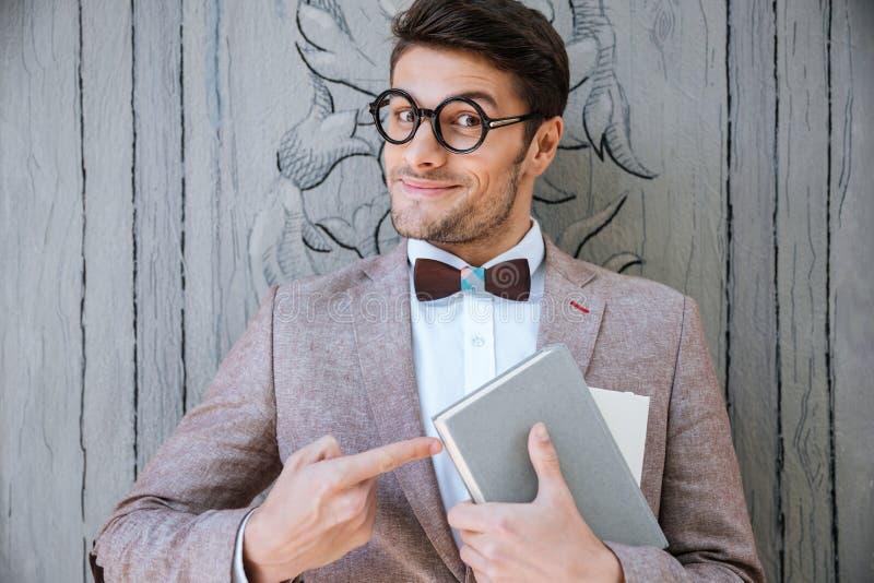 Χαριτωμένο αστείο άτομο στα στρογγυλά γυαλιά που δείχνει στο βιβλίο στοκ εικόνες με δικαίωμα ελεύθερης χρήσης