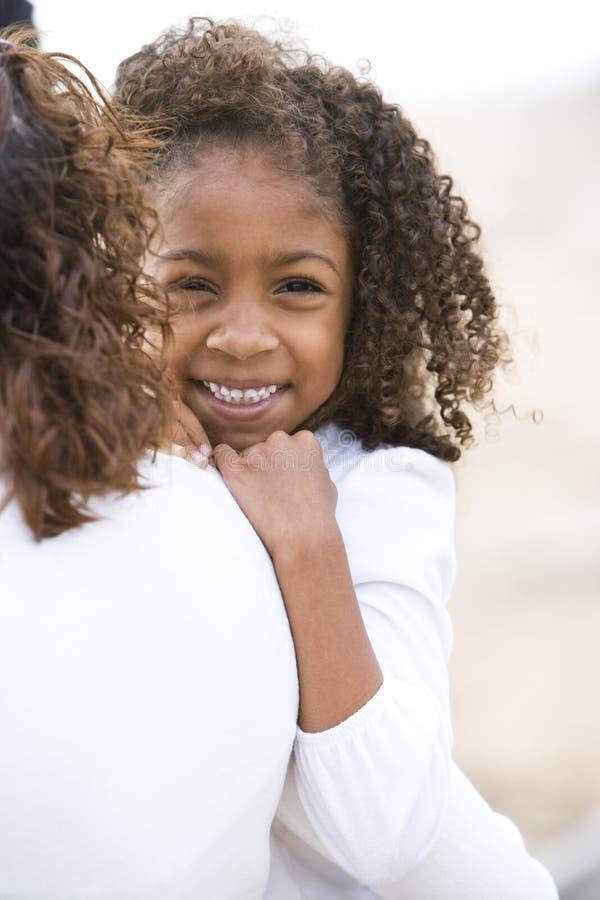 Χαριτωμένο αφρικανικός-αμερικανικό κορίτσι κινηματογραφήσεων σε πρώτο πλάνο στα όπλα των mom στοκ φωτογραφίες