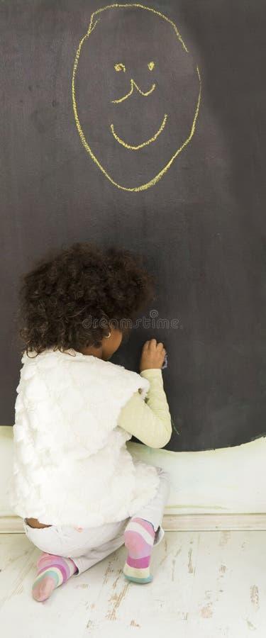 Χαριτωμένο αφρικανικό κορίτσι μπροστά από τον πίνακα στοκ εικόνα με δικαίωμα ελεύθερης χρήσης