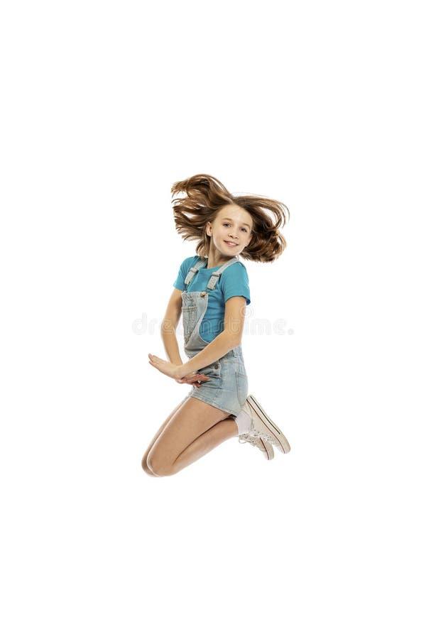 Χαριτωμένο γελώντας κορίτσι εφήβων στο άλμα, που απομονώνεται στο άσπρο υπόβαθρο στοκ εικόνες