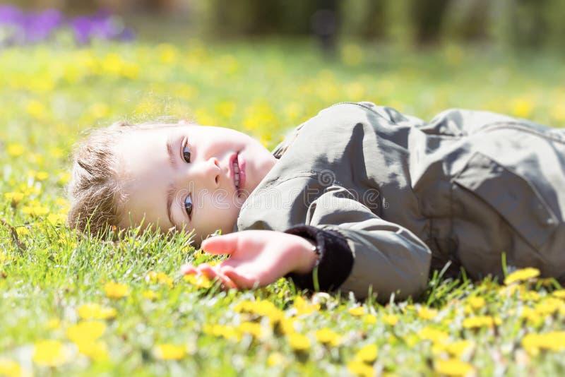 Χαριτωμένο γλυκό μικρό κορίτσι που βάζει την άνοιξη τη χλόη με τις μαργαρίτες στοκ φωτογραφία