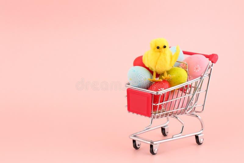 Χαριτωμένο διακοσμητικό κοτόπουλο σε έναν σωρό των ζωηρόχρωμων χρωματισμένων αυγών σε ένα κάρρο αγορών στο ρόδινο κλίμα με ένα δι στοκ εικόνα