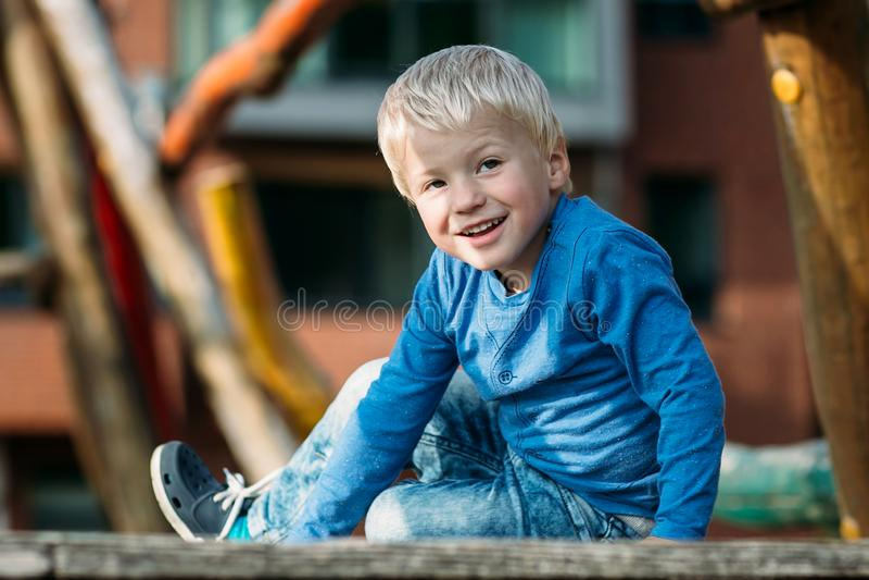 Χαριτωμένο ευτυχές αγοράκι με τα ξανθά μαλλιά που έχουν τη διασκέδαση στην παιδική χαρά στοκ εικόνες