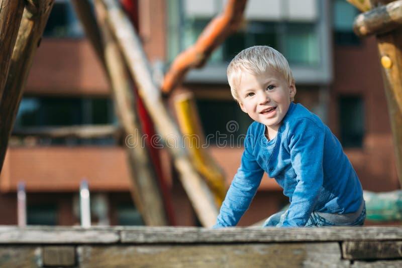 Χαριτωμένο ευτυχές αγοράκι με τα ξανθά μαλλιά που έχουν τη διασκέδαση στην παιδική χαρά στοκ φωτογραφία με δικαίωμα ελεύθερης χρήσης