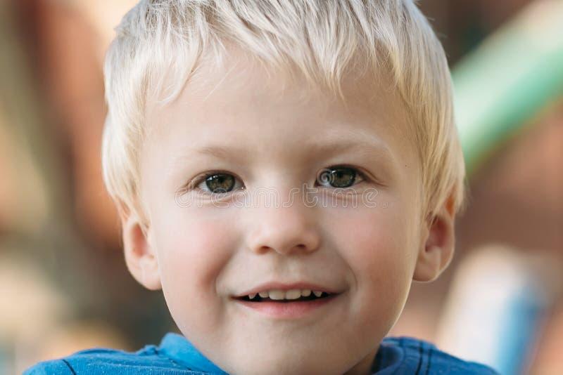 Χαριτωμένο ευτυχές αγοράκι με τα ξανθά μαλλιά που έχουν τη διασκέδαση στην παιδική χαρά στοκ φωτογραφία
