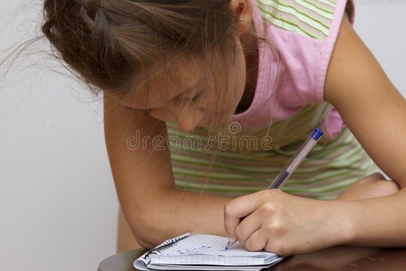 Χαριτωμένο ευτυχές μικρό κορίτσι που γράφει κάτι στο σημειωματάριό της στοκ εικόνες με δικαίωμα ελεύθερης χρήσης