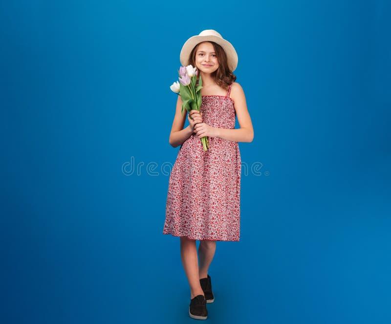 Χαριτωμένο ευτυχές μικρό κορίτσι που στέκεται και που κρατά τις φρέσκες τουλίπες στοκ εικόνες με δικαίωμα ελεύθερης χρήσης