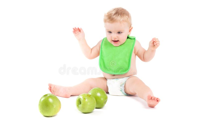 Χαριτωμένο ευτυχές μικρό παιδί στο πράσινο παιχνίδι των ετερόφθαλμων γάδων με τα μήλα στοκ φωτογραφία