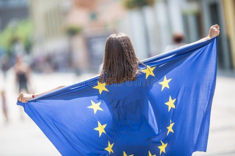 Χαριτωμένο ευτυχές νέο κορίτσι με τη σημαία της Ευρωπαϊκής Ένωσης στις οδούς κάπου στην Ευρώπη στοκ φωτογραφίες με δικαίωμα ελεύθερης χρήσης