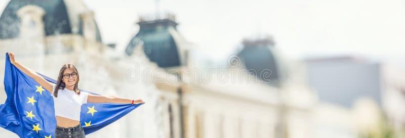 Χαριτωμένο ευτυχές νέο κορίτσι με τη σημαία της Ευρωπαϊκής Ένωσης μπροστά από ένα ιστορικό κτήριο κάπου στην Ευρώπη στοκ εικόνες