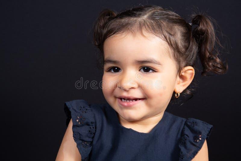 Χαριτωμένο ευτυχές νέο κορίτσι που φαίνεται πλευρά στο μαύρο υπόβαθρο στοκ εικόνες