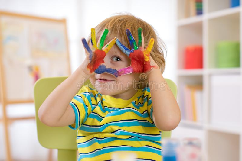 Χαριτωμένο εύθυμο αγόρι παιδιών που παρουσιάζει χέρια που χρωματίζονται στα φωτεινά χρώματα στοκ φωτογραφίες με δικαίωμα ελεύθερης χρήσης